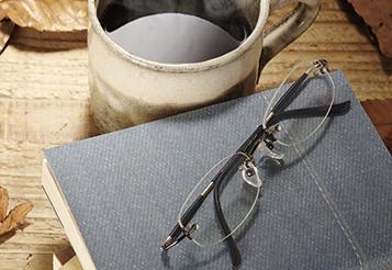 Seitenbild_KKW19_F10_AdobeStock-74001988_Kaffee-Buch-Brille-Holztisch-Laub