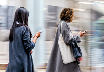 Kopp-Kirsamer – Seitenbild_KKW20_F05_AdobeStock-131258965_Zwei-Frauen-mit-Smartphones-laufend-an-Straße-entlang